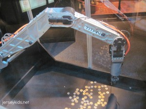Try your hand at picking up coins using a robotic arm. Copyright Deborah Abrams Kaplan