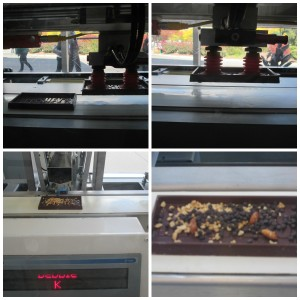 The machine uses suction to pick up the candy bar base and put it on the conveyor belt. Machines deposit the toppings in the bar. Copyright Deborah Abrams Kaplan